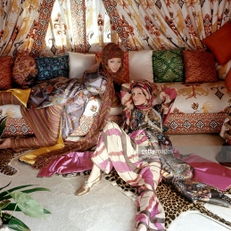 Models Vivianne and Christiana, reclining on the sofa and leopard-print rugs, wearing elaborate silk print Turquerie coats by Valentino with turbans and scarves in the tent room in the Rome apartment of fashion designer Valentino *** Local Caption ***